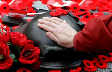 A woman places her hand on the Tomb of the Unknown Soldier following Remembrance Day ceremonies at the National War Memorial in Ottawa